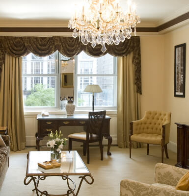 Under the glow of a chandelier, City View Suite #207 flaunts buttery tones for stylish elegance.