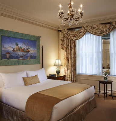 Rest easy in a king size bed under an ornate chandelier while staying in Interior Suite #815.