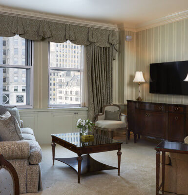 Suite #711 features a living room with a view of the city, a comfortable couch and flat screen TV.